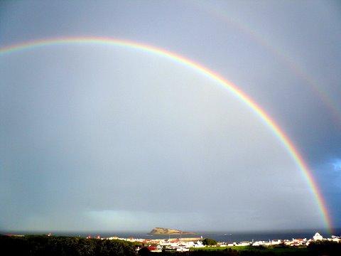 Regenbogen über der Ilhéu da Praia
